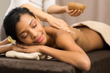 Spa therapist applying scrub salt on young woman back at salon spa