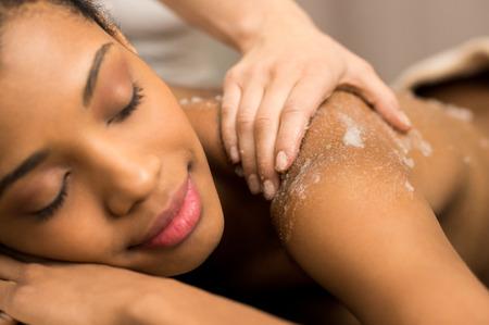 Photo pour Spa therapist applying massage salt on young woman back at spa - image libre de droit
