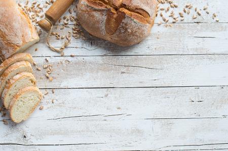 Foto de Loafs of bread and rolling pin on rustic table with grain - Imagen libre de derechos