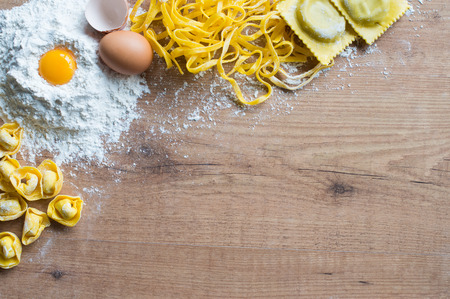 Photo pour Tortellini, tagliatelle and tortelloni on table with the ingredients - image libre de droit