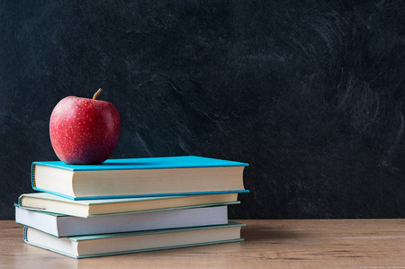 Photo for Apple and a stack of books on desk with blackboard in background - Royalty Free Image
