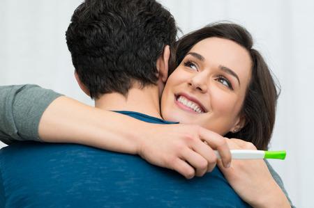 Foto de Closeup of happy young woman embracing man after positive pregnancy test - Imagen libre de derechos