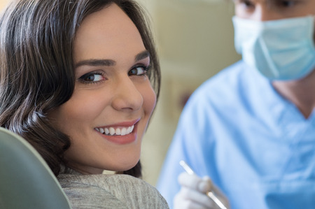 Foto per Smiling young woman receiving dental checkup - Immagine Royalty Free
