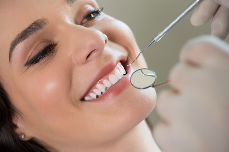 Foto per Closeup of dentist examining young woman's teeth - Immagine Royalty Free