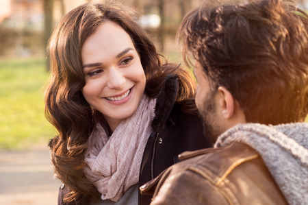 Photo pour Portrait of happy couple looking at each other and smiling outdoor - image libre de droit