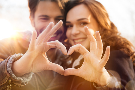 Photo pour Closeup of couple making heart shape with hands - image libre de droit