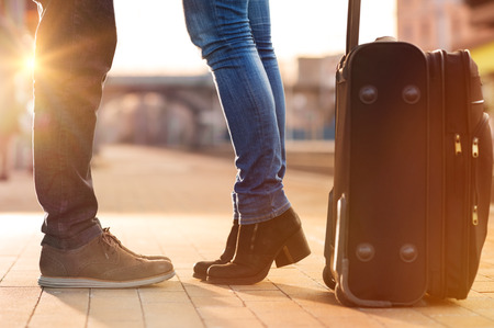 Foto de Closeup shot of woman feet standing on tiptoe while embracing her man at railway platform for a farewell before train departure. A travelling luggage is on the foreground. Beautiful warm sunset light and flare are coming from the background. - Imagen libre de derechos