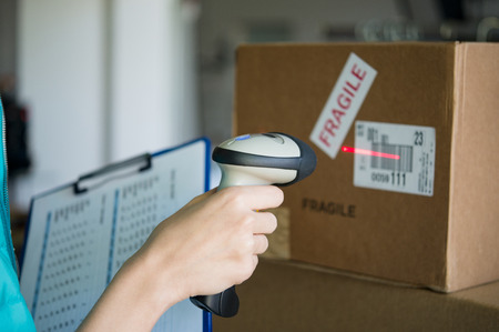Photo for Closeup shot of worker scanning box with barcode reader. Reading and Scanning labels on the boxes with bluetooth barcode scanner in a warehouse. Shallow depth of field with focus on scanning box with barcode reader. - Royalty Free Image