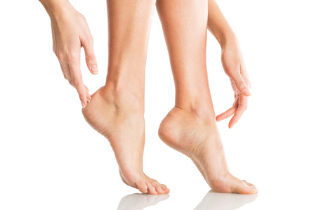 Foto de Closeup shot of a woman applying moisturizer to her leg and feet. Beauty feet and hands isolated on white background. Young woman touching hands and legs with french manicured nails. - Imagen libre de derechos