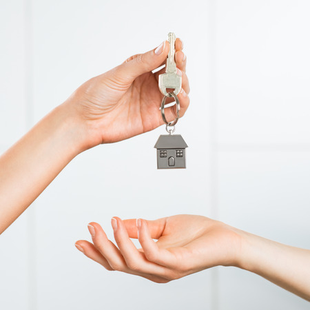 Foto de Closeup shot of a female hand receiving house key. Woman buying new home. Close up hand holding house key. - Imagen libre de derechos