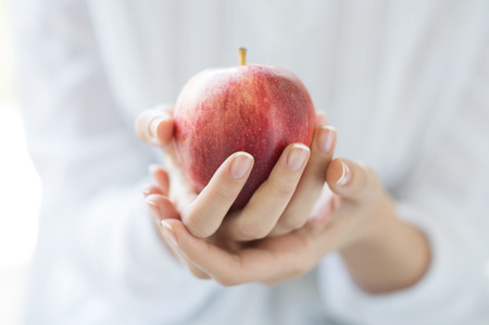 Photo for Closeup shot of a woman holding healthy red apple. Red apple in woman hands with white shirt at home. Shallow depth of field with focus on the red apple. - Royalty Free Image