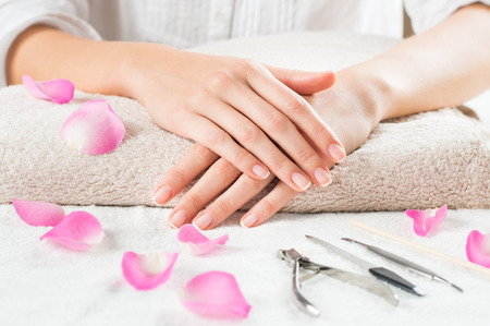 Photo pour Closeup shot of female hands with french manicure on a towel surrounded by petals and manicure set. Woman getting nail manicure. Shallow depth of field with focus on woman hand. - image libre de droit