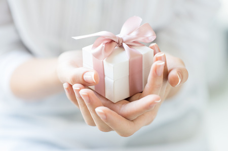 Photo pour Close up shot of female hands holding a small gift wrapped with pink ribbon. Small gift in the hands of a woman indoor. Shallow depth of field with focus on the little box. - image libre de droit