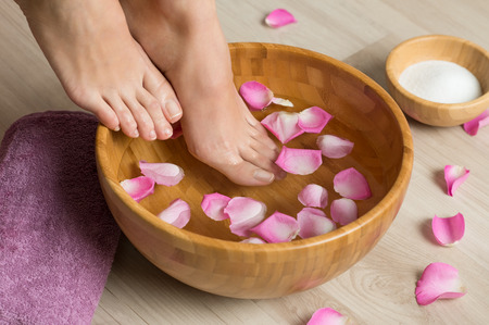Photo pour Closeup shot of a woman feet dipped in water with petals in a wooden bowl. Beautiful female feet at spa salon on pedicure procedure. Shallow depth of field with focus on feet. - image libre de droit