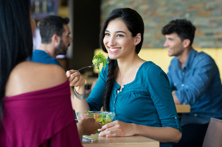 Photo pour Closeup shot of young women eating salad at restaurant. Happy female friends smiling and chatting. Portrait of smiling girl holding a forkful of salad during lunch break. - image libre de droit