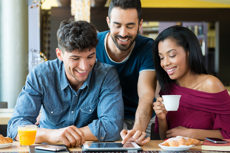 Photo pour Closeup shot of happy young friends using digitaltablet during breakfast. Smiling men and woman doing breakfast at coffee bar. Happy young friends looking at palmtop and having a joyful breakfast. - image libre de droit