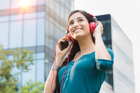Foto de Closeup shot of young woman listening to music with mobile phone in the city center. Happy smiling girl listening to music with professional red headset. Beautiful brunette young woman feeling free and thinking. - Imagen libre de derechos