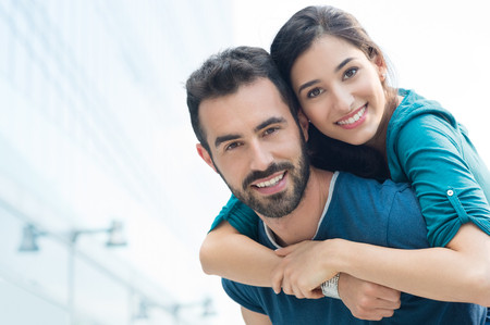 Photo for Closeup shot of young man carrying young woman on his back. Happy smiling couple looking at camera. Happy couple putdoor having fun piggyback in love. - Royalty Free Image