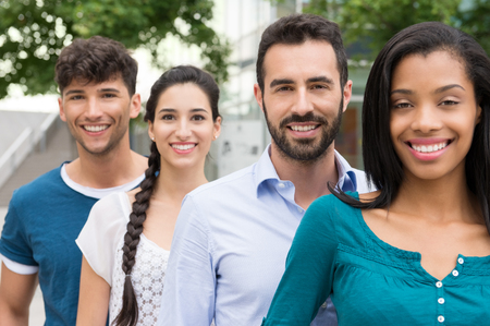 Photo pour Closeup shot of young friends standing in a row outdoor. Happy group of men and women smiling and looking at camera. Happy young friends outside. - image libre de droit