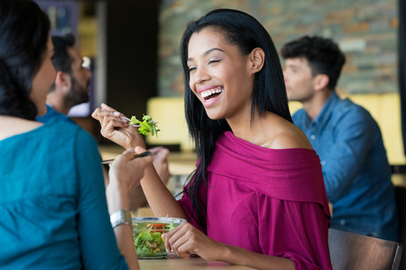 Photo pour Closeup shot of young woman eating salad with her friend. African girl smiling at lunch. Lughing woman eating salada at restaurant during her lunch break. - image libre de droit