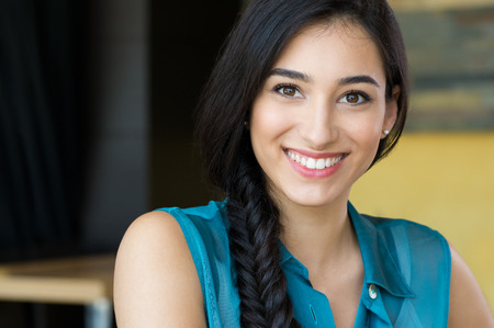 Foto de Closeup shot of young woman smiling. Portrait of brunette girl looking at camera and smiling. Shallow depth of field with focus on beautiful young happy girl with braid smiling. - Imagen libre de derechos