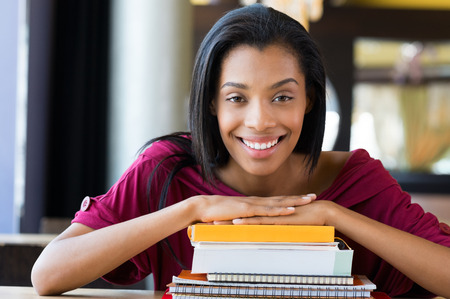 Foto de Closeup shot of young woman lies on stack of books. Happy female student smiling and looking at camera. Shallow depth of field with focus on young african woman rests on stack of books. - Imagen libre de derechos