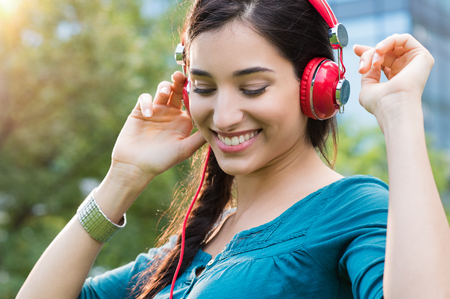 Photo for Closeup shot of young woman listening to music in a park. Portrait of happy smiling girl feeling free with music. Close up face of beautiful latin girl listening to music with professional headphone and dancing in a city center. - Royalty Free Image