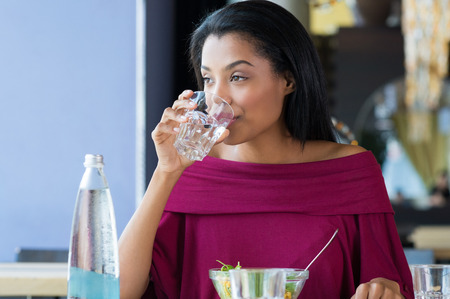 Photo pour Closeup shot of young woman drinking a glass of water. African girl drinking water durinh her lunch break at restaurant. a Beautiful girl thirsty drink a glass of water and looking away. - image libre de droit