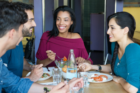 Photo for Closeup shot of young women and men having meal. Friends looking at eachother during the lunch. Smiling young friends eating together at restaurant in a summer day. - Royalty Free Image