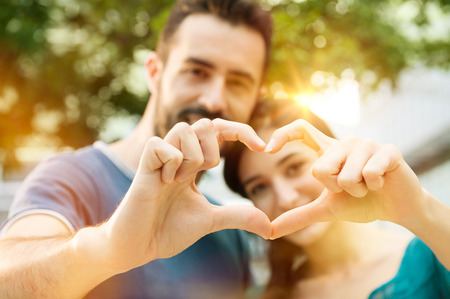 Foto de Closeup shot of young man and woman making heart shape with hand. Loving couple making heart shape with hands outdoor. Female and male hands making up heart shape. - Imagen libre de derechos