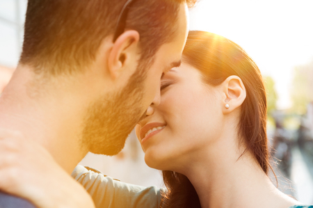 Foto de Closeup shot of young couple kissing outdoor. Close up of loving couple embracing and kissing. Shallow depth of field with focus on young couple kissing. - Imagen libre de derechos