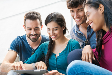 Foto de Closeup shot of young men and women looking at digitaltablet. Happy smilin friends sitting outdoor using digital tablet.   Happy young woman pointing on a digital tablet. - Imagen libre de derechos