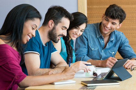Foto de Closeup shot of young man and woman discussing on note. Happy smiling students preparing the exam. Team of students studying together for the university exam. - Imagen libre de derechos
