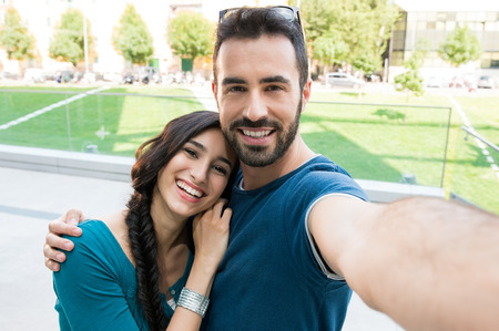 Photo pour Closeup shot of young couple take selfie outdoor. Young man taking a photo with his girlfriend. Happpy smiling couple taking a selfie in a summer day. - image libre de droit