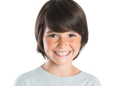 Photo for Closeup shot of little boy smiling with freckles. Portrait of happy male child looking at camera isolated on white background. Happy cute boy with brown hair standing against white background. - Royalty Free Image