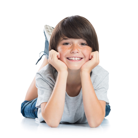 Foto de Closeup of smiling little boy with freckles lying on white background. Happy cute male child lying on white floor and looking at camera. Portrait of a smart young boy. Adorable caucasian kid lying with hands on chin. - Imagen libre de derechos