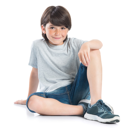 Photo pour Closeup shot of smiling little boy sitting on white background. Adorable child in casual looking at camera. Happy cute boy sitting on floor and looking at camera. - image libre de droit