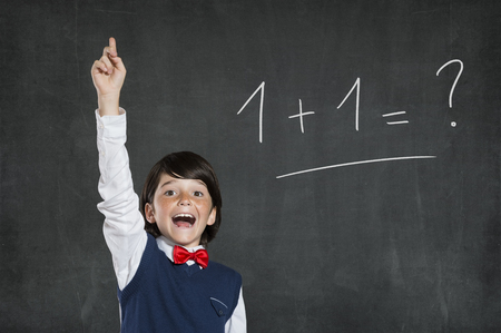 Foto de Little scholar boy knows the solution of this easy problem. Schoolboy pointing high his index finger. Cheerful cute boy with raised hand standing against black background. - Imagen libre de derechos