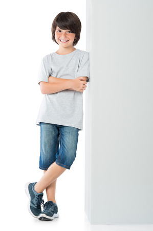 Photo pour Smiling little boy posing against grey wall isolated on white background. Happy cute child standing against white background. Young boy leaning against a grey sign and looking at camera with arms crossed. - image libre de droit