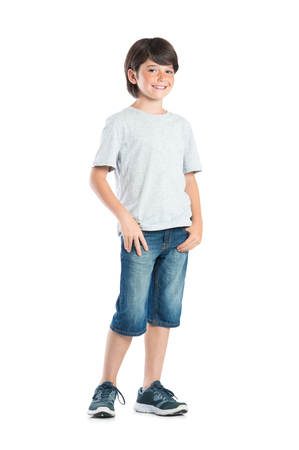 Photo pour Smiling little boy with freckles standing isolated on white background. Portrait of satisfied cute child in casual clothes looking at camera. Happy cute boy with hand in pocket standing against white background. - image libre de droit