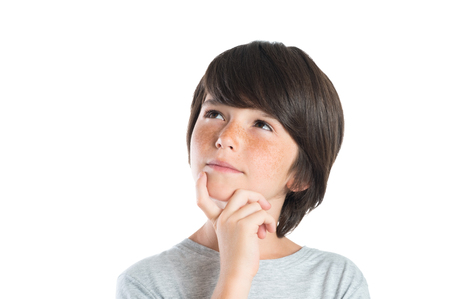 Foto de Portrait of cute boy thinking isolated on white background. Closeup shot of boy thinking with hand on chin. Male child with freckles looking up and contemplates isolated on white background. - Imagen libre de derechos