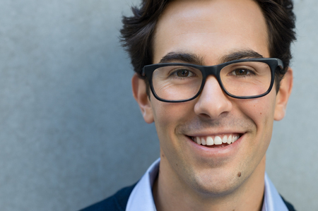 Photo pour Young man smiling and looking at camera wearing glasses. Portrait of a happy handsome young man wearing spectacles with grey background. Close up of young cool trendy man with glasses and copy space. - image libre de droit