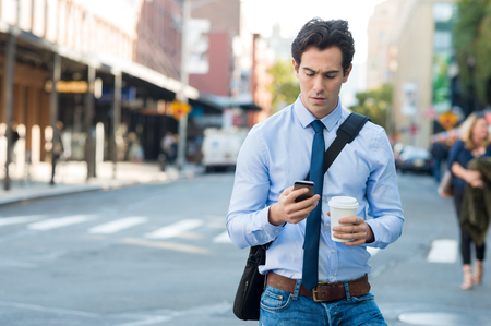 Photo pour Businessman using smartphone and holding paper cup ina urban scene. Worried businessman in walking on the road and messaging with phone. Young man text messaging through cell phone while walking on the road in the city centre. - image libre de droit