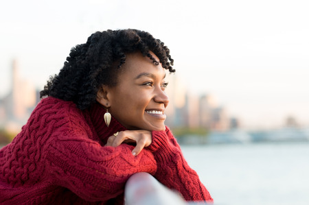 Foto de Close up portrait of a young happy african woman leaning on the banister of a bridge near river. Happy young african woman at river side thinking about the future. Smiling pensive girl looking across river at sunset. - Imagen libre de derechos