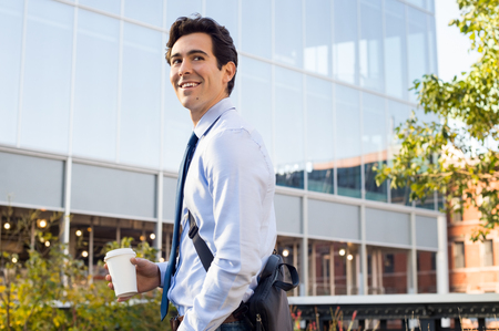 Photo pour Happy young businessman walking and holding laptop bag and coffee paper cup. Satisfied businessman looking away with modern buildings in background. Happy smiling man going to work with a take away coffee in a paper cup. - image libre de droit