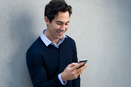 Foto de Close up of a young man leaning against a grey wall using mobile phone. Portrait of a happy business man holding a smartphone. Man in casual typing and reading a message on cell phone with copy space. - Imagen libre de derechos