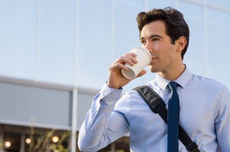 Photo for Successful young businessman drinking a take away coffee outside office. Businessman drinking coffee and thinking about his future. Happy ambitious man drinking an hot coffee with a paper cup in front of the modern building. - Royalty Free Image