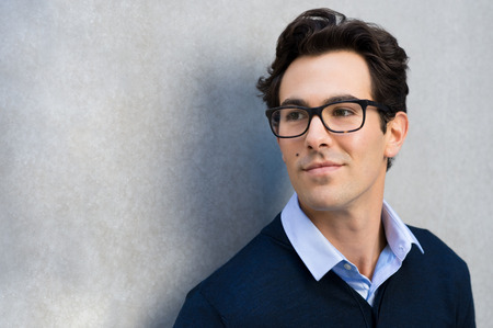 Foto de Smiling guy wearing glasses looking away and leaning on grey wall. Handsome young business man in casual wearing goggles and thinking. Portrait of young businessman with eyeglasses thinking about his carrer with copy space. - Imagen libre de derechos