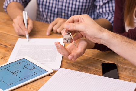 Photo for Happy young couple getting keys of their new house. Close up of female hand receiving keys from house broker. Closeup of the hand of a real estate agent who give the house keys to a woman while her boyfriend signing a contract. - Royalty Free Image