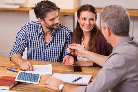 Photo pour Young happy couple receiving house keys from real estate agent. Giving keys of new house to young couple. Smiling couple signing financial contract for mortgage. - image libre de droit